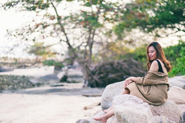 Eine schöne asiatische frau genießt es, auf dem felsen an der küste zu sitzen Premium Fotos