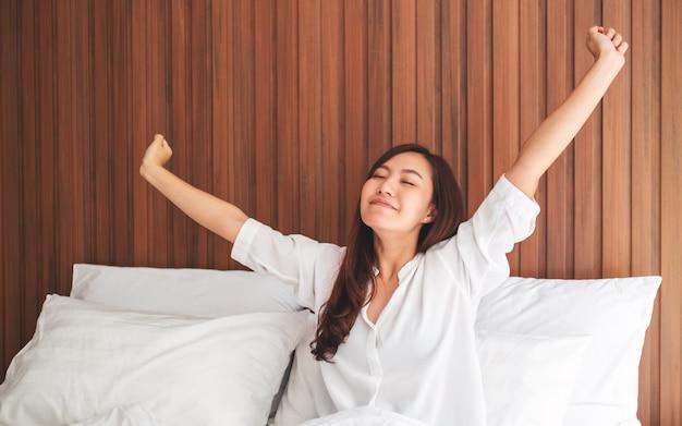 Eine schöne asiatische frau streckt sich, nachdem sie morgens auf einem weißen gemütlichen bett zu hause aufgewacht ist Premium Fotos