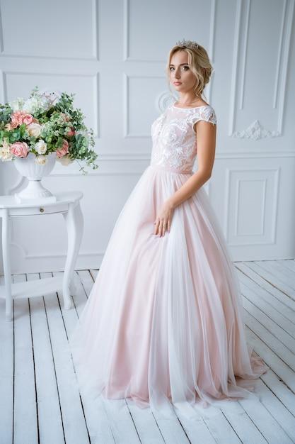 Eine schöne braut mit haaren und make-up steht in einem zarten rosa hochzeitskleid in einem hellen dekor mit blumen Kostenlose Fotos