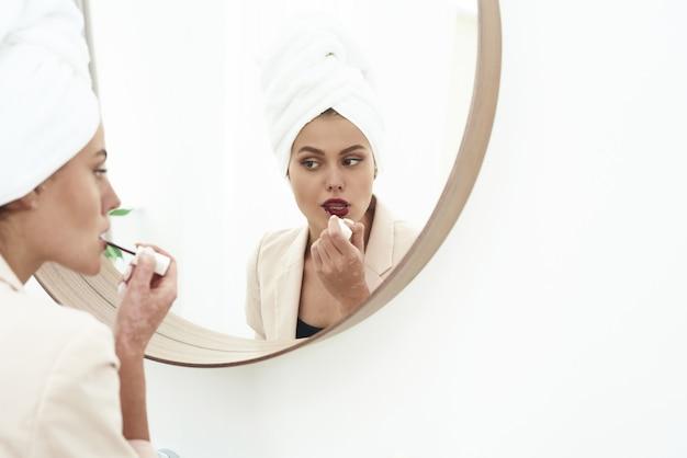 Eine schöne brünette steht in einem anzug im badezimmer und malt ihre lippen am morgen vor der arbeit mit einem matten dunklen lippenstift. Premium Fotos