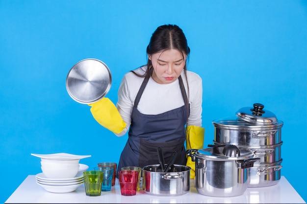 Eine schöne frau beim abwasch vor ihm auf einem blauen hintergrund. Kostenlose Fotos