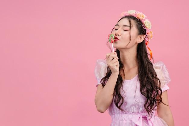 Eine schöne frau, die in einer rosa prinzessin gekleidet wird, spielt mit ihrer süßen süßigkeit auf einem rosa. Kostenlose Fotos