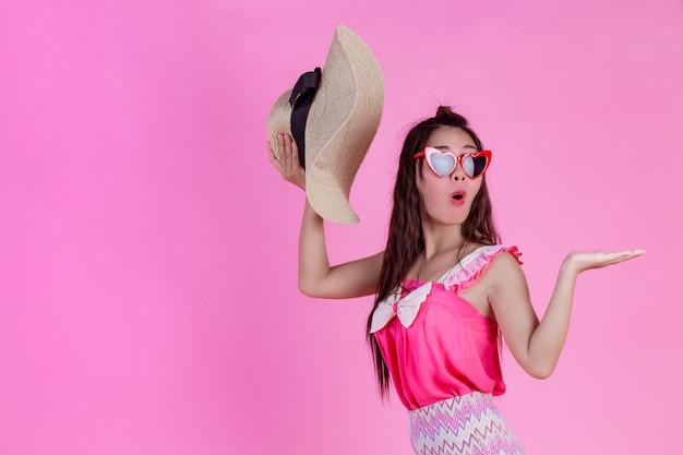 Eine schöne frau, die rote gläser mit einem großen hut auf einem rosa trägt. Kostenlose Fotos