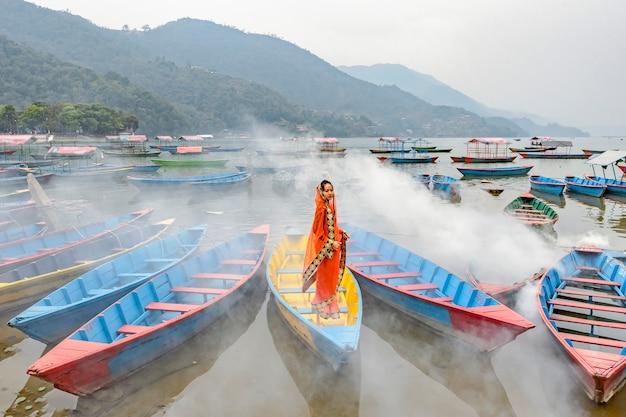 Eine schöne frau in einem sarianzug steht auf einem boot in pokhara nepal. Premium Fotos