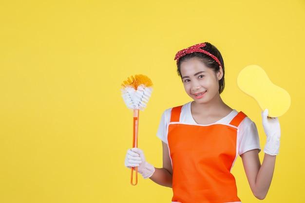 Eine schöne frau mit einem reinigungsgerät auf einem gelb Kostenlose Fotos
