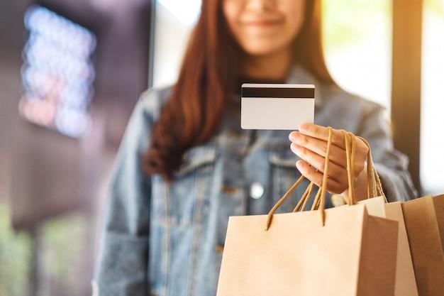 Eine schöne frau mit einkaufstüten, die eine kreditkarte für den kauf halten und verwenden Premium Fotos