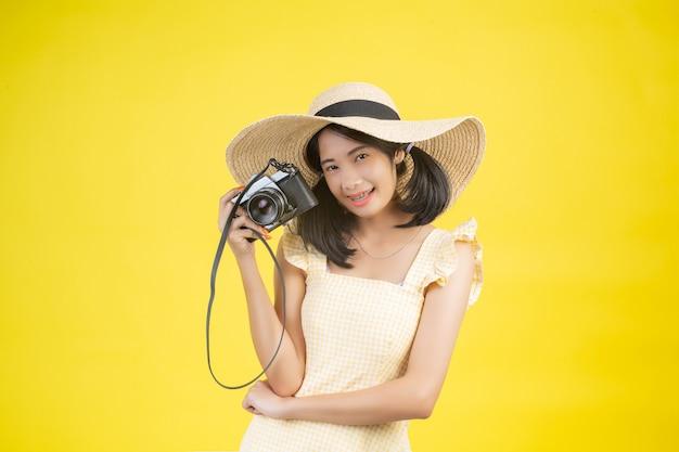 Eine schöne, glückliche frau, die einen großen hut und eine kamera auf einem gelb trägt. Kostenlose Fotos