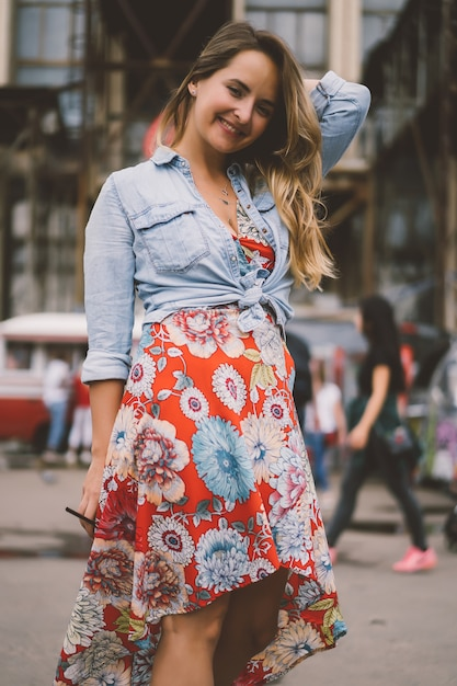Eine schöne junge frau mit langen haaren mit einem glas kaffee lächelt und lacht. Kostenlose Fotos