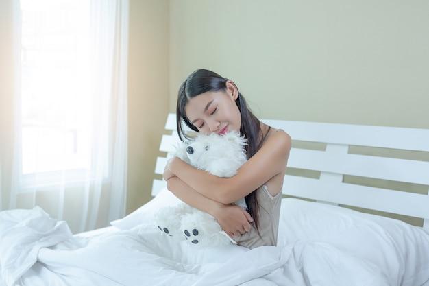 Eine schöne junge frau schläft und ein wecker im schlafzimmer zu hause. Kostenlose Fotos