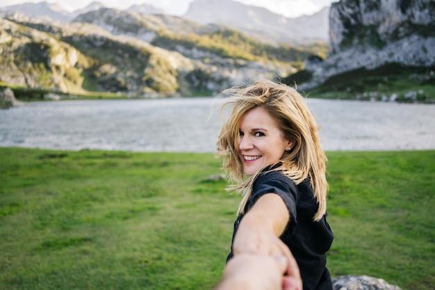 Eine schöne kaukasische blonde frau hält die hand eines mannes in einer gebirgslandschaft mit see Premium Fotos