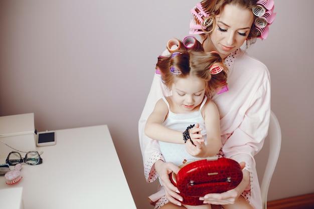 Eine schöne und stilvolle mutter macht ihre frisur für sie und ihre kleine tochter Premium Fotos