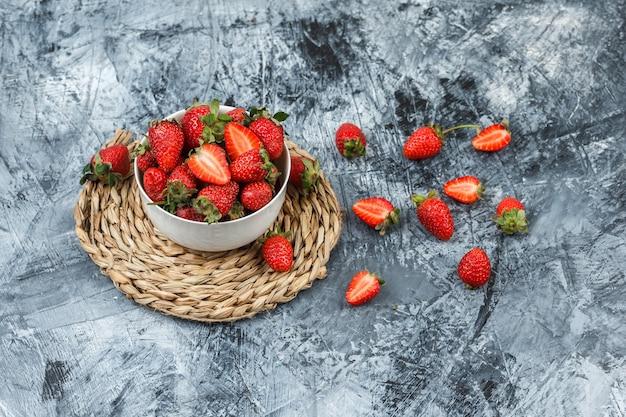 Eine schüssel erdbeeren auf einem runden weiden-tischset auf einem dunkelblauen marmorhintergrund. . Kostenlose Fotos