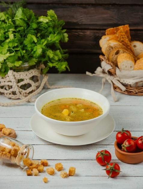 Eine schüssel hühnersuppe mit kartoffeln, karotten und dill, serviert mit brotscheiben Kostenlose Fotos