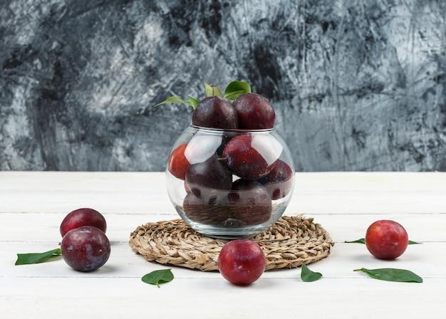 Eine schüssel pflaumen auf einem tischset aus korbweide auf einem hintergrund aus dunkelblauem marmor und weißem holzbrett. nahansicht. Kostenlose Fotos