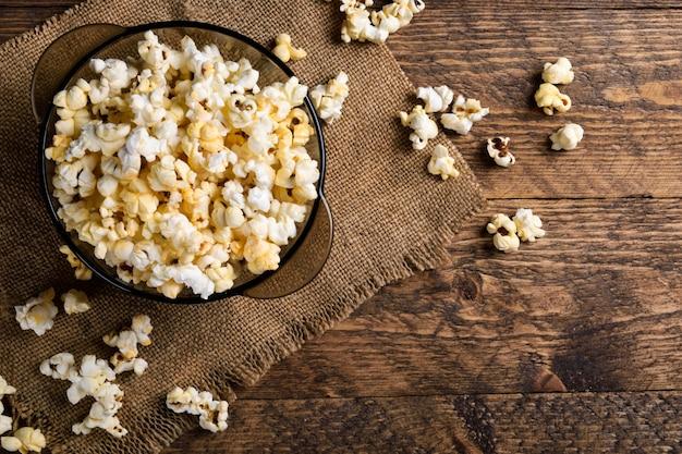 Eine schüssel popcorn auf einem holztisch Premium Fotos