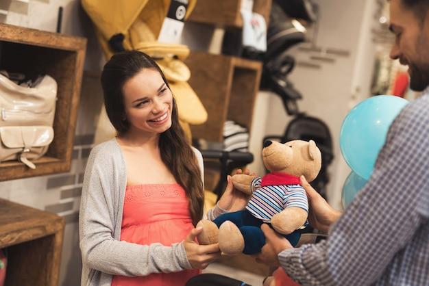 Eine schwangere frau zusammen mit einem mann wählen sie einen teddybär. Premium Fotos