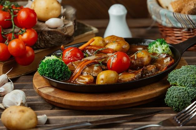 Eine schwarze kupferne platte der gemischten gegrillten nahrungsmittel und des gemüses. Kostenlose Fotos