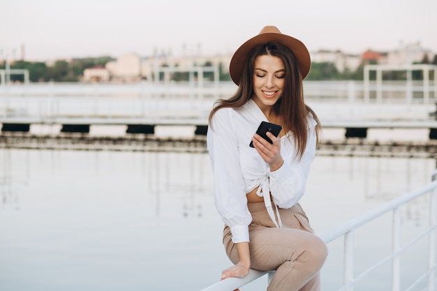 Eine stilvolle frau, die telefonisch spricht und entlang die strandpromenade an einem warmen sommertag bei sonnenuntergang geht Premium Fotos
