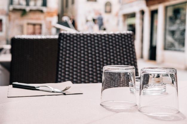 Eine tabelle eines straßen- und sommercafés mit tischbesteck mit einer anlage auf dem tisch. Premium Fotos