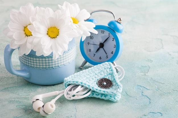 Eine tasse, ein blauer wecker und blumen Premium Fotos