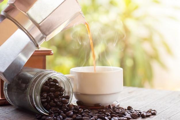 Eine tasse heiße espresso-kaffeetassen und geröstete kaffeebohnen mit moka-kanne auf holzbodenhintergrund, kaffeemorgen, selektiver fokus Premium Fotos