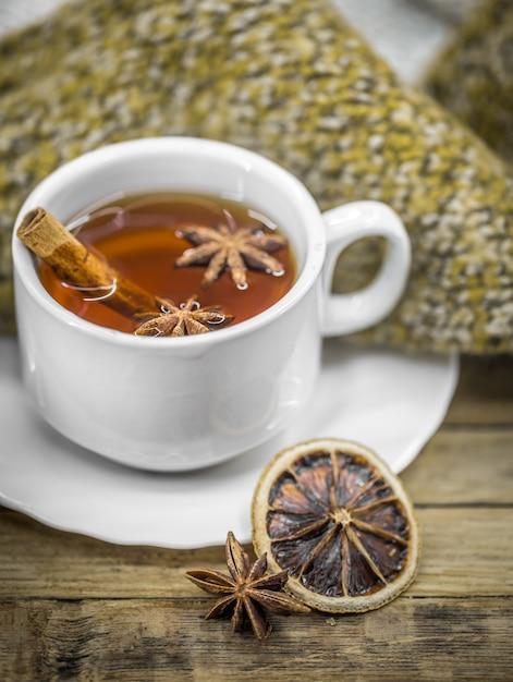 Eine tasse heißen tee mit zimtstangen, gewürzen und köstlicher getrockneter zitrone auf holz mit einem warmen pullover Kostenlose Fotos