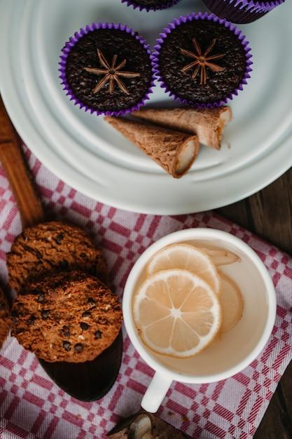 Eine tasse ingwer-zitronen-tee mit keksen und brownies. Kostenlose Fotos