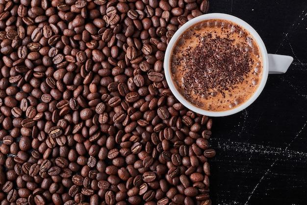 Eine tasse kaffee auf braunen bohnen. Kostenlose Fotos