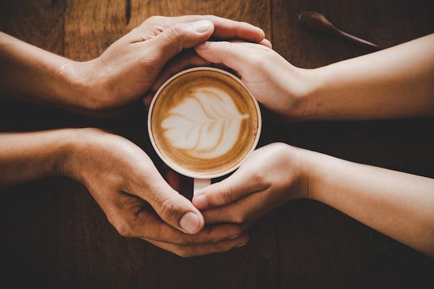 Eine tasse kaffee in den händen eines mannes und einer frau. tiefenschärfe. Kostenlose Fotos