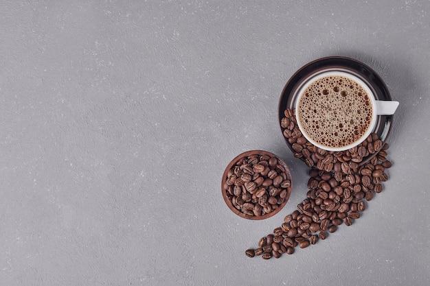 Eine tasse kaffee mit arabica-bohnen herum, draufsicht. Kostenlose Fotos