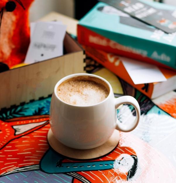 Eine tasse kaffee mit büchern auf dem tisch Kostenlose Fotos