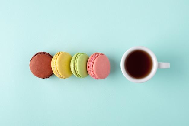 Eine tasse kaffee mit bunten macarons auf blauer oberfläche Premium Fotos