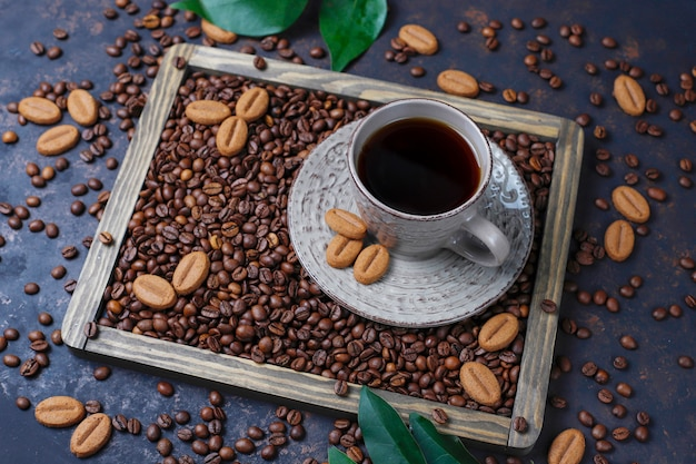 Eine tasse kaffee mit gerösteten kaffeebohnen und kaffeebohnen formte plätzchen auf dunkler oberfläche Kostenlose Fotos
