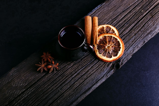 Eine tasse kaffee, sternanis, zimt, getrocknete orange und kaffeebohnen auf einer dunklen küchenarbeitsplatte Premium Fotos