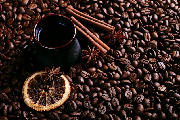 Eine tasse kaffee, sternanis, zimt und getrocknete orange auf kaffeebohnen Premium Fotos