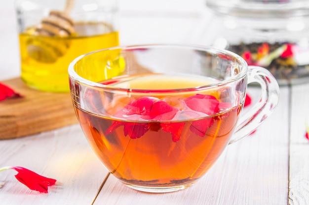 Eine tasse tee, im hintergrund eine bank von honig und ein glas mit einem schwarzen Premium Fotos