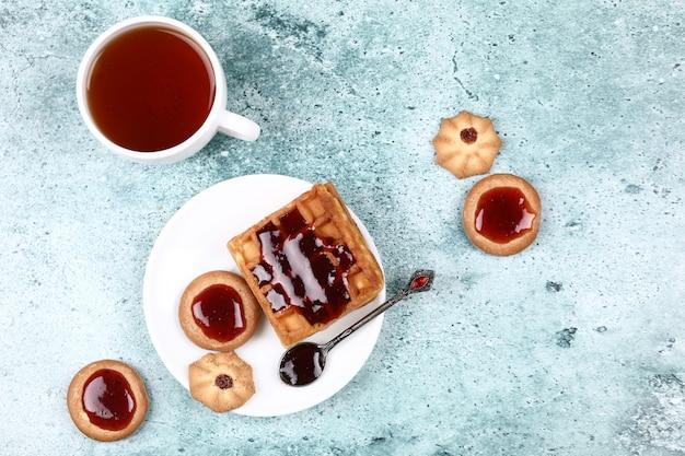 Eine tasse tee, kekse und waffel mit erdbeermarmelade. Kostenlose Fotos