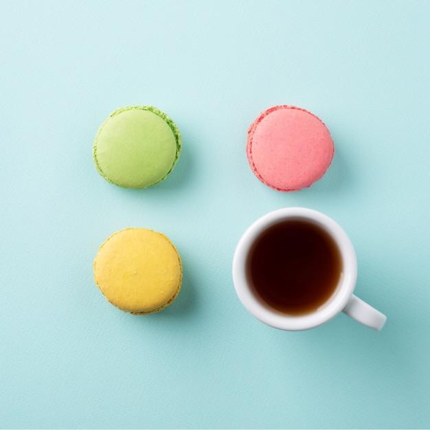 Eine tasse tee mit bunten macarons auf hellblauer oberfläche Premium Fotos