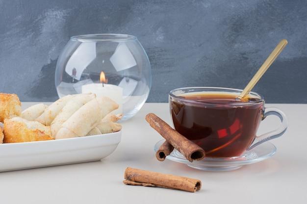 Eine tasse tee mit zimt und keksen auf weißem tisch. Kostenlose Fotos