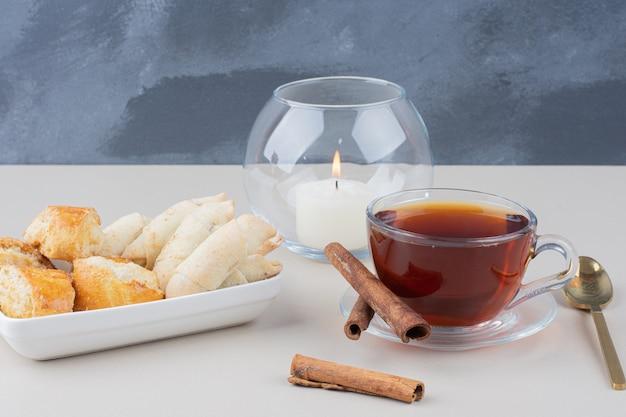 Eine tasse tee mit zimt und verschiedenen keksen auf weißer oberfläche. Kostenlose Fotos