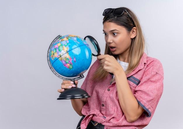 Eine überraschte junge frau, die rotes hemd in der sonnenbrille trägt, die einen globus hält, während sie ihn mit lupe betrachtet Kostenlose Fotos