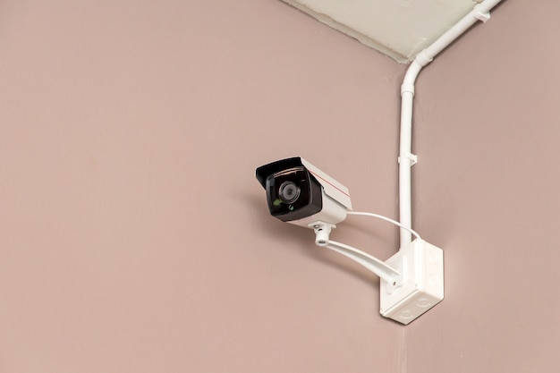 Eine überwachungskamera an der wand im inneren des gebäudes, die unter wichtigen ereignissen überwacht Premium Fotos