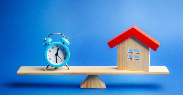 Eine uhr und ein miniaturhaus auf der waage Premium Fotos