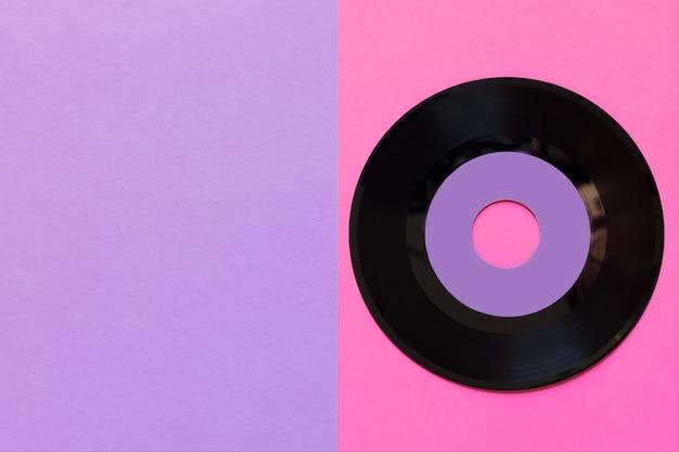 Eine veraltete vinylplatte auf einem zwei-tonnen-papierhintergrund: rosa und violett, popkultur. Premium Fotos