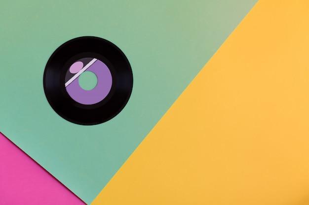 Eine veraltete vinylscheibe auf einem drei-tonnen-papierhintergrund, popkultur. Premium Fotos