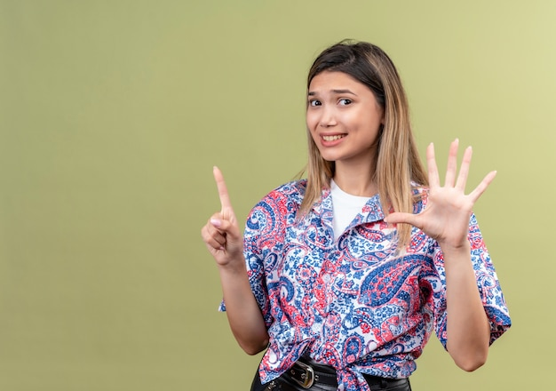 Eine verwirrte junge frau, die ein paisley-bedrucktes hemd trägt, das nummer sechs zeigt Kostenlose Fotos