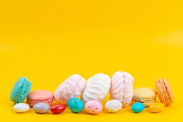 Eine vorderansicht baiser und macarons köstlich und süß auf gelben, farbigen regenbogenbonbons Kostenlose Fotos