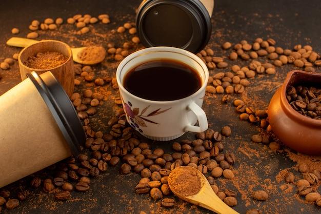 Eine vorderansicht braune kaffeesamen mit schokoriegeln und einer tasse kaffee über die dunkle oberfläche und kaffeesamenkorngranulat Kostenlose Fotos