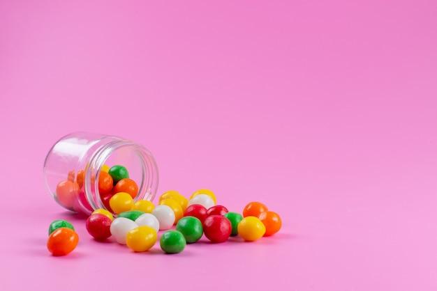 Eine vorderansicht bunte bonbons süß und klebrig auf rosa, farbe zucker süßwaren süßwaren Kostenlose Fotos