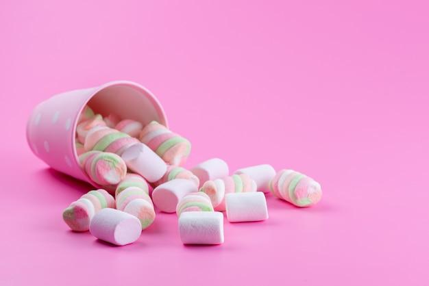 Eine vorderansicht, die marshmallow kaut, süß und köstlich auf rosa, süßer zuckerfarbe Kostenlose Fotos